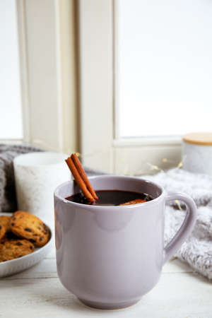 Cup of hot mulled wine on window sill. Winter drink