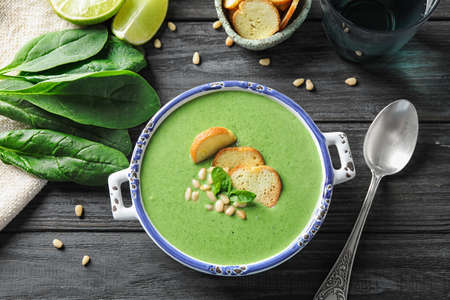 Bowl of healthy green soup with fresh spinach on grey wooden table, flat lay Stockfoto