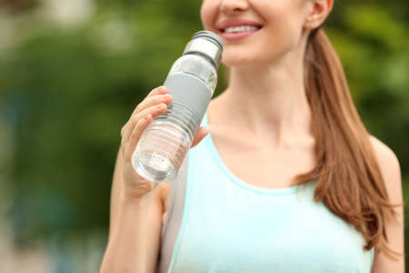 Young woman with bottle of water outdoors, closeup. Refreshing drink Zdjęcie Seryjne