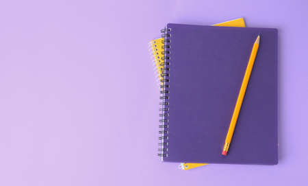 Notebooks with pencil on lilac background, top view. Space for text