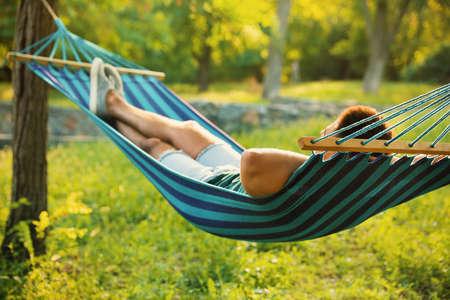 Young man resting in comfortable hammock at green garden Stock fotó