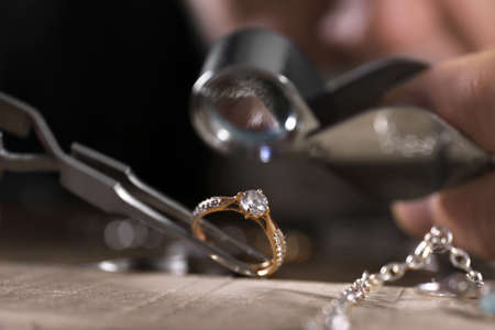 Male jeweler examining diamond ring in workshop, closeup view Stok Fotoğraf - 130073829
