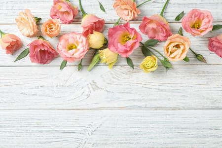 Flat lay composition with beautiful Eustoma flowers on white wooden table, space for text