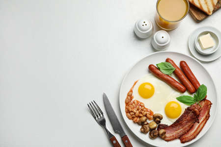 Traditional English breakfast with fried eggs on light table, flat lay. Space for text Zdjęcie Seryjne