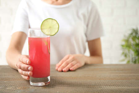 Young woman with glass of tasty refreshing drink at wooden table, closeup