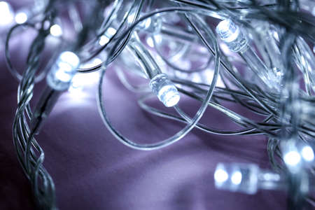 Glowing Christmas lights on violet background, closeup