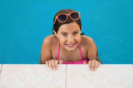 Happy cute girl with sunglasses in swimming pool