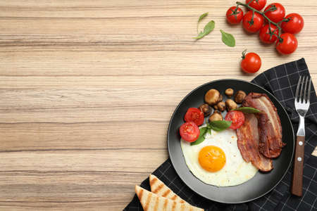 Tasty breakfast with fried egg served on wooden table, flat lay. Space for text