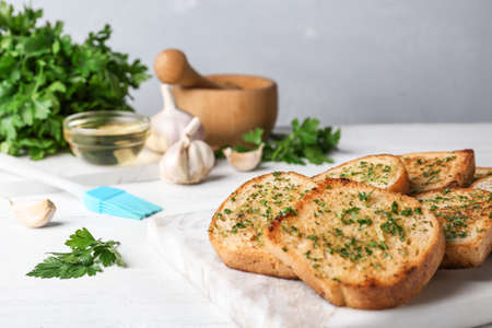 Slices of toasted bread with garlic and herbs on white wooden table