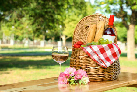 Composition with picnic basket on table outdoors