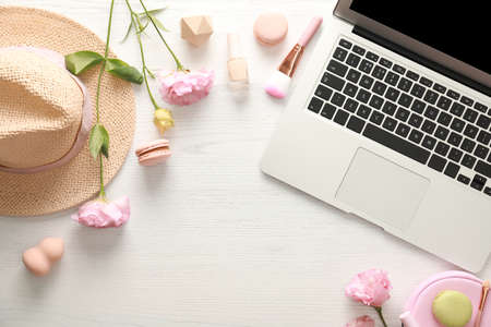 Flat lay composition with laptop, makeup products and accessories on white wooden table.