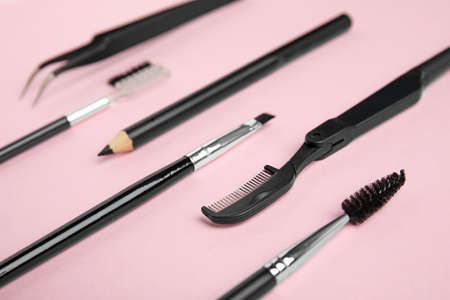 Set of professional eyebrow tools on pink background