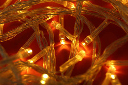 Glowing Christmas lights on red background, closeup