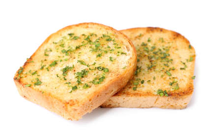 Slices of toasted bread with garlic and herbs on white background Imagens