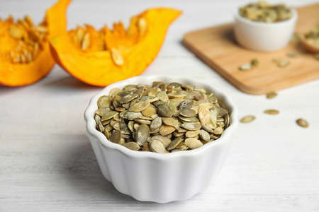 Bowl of raw pumpkin seeds on white wooden table Stock fotó