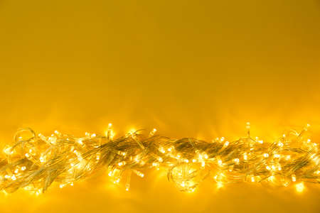 Glowing Christmas lights on yellow background, top view. Space for text