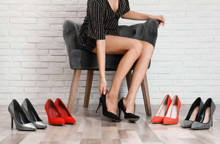 Woman trying on different shoes near white brick wall, closeup