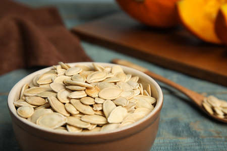 Bowl of raw pumpkin seeds on blue wooden table, closeup. Space for text