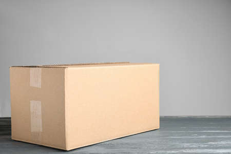 Cardboard box on grey wooden table against beige background, space for text