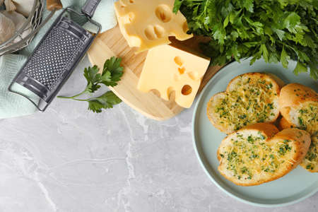 Slices of toasted bread with garlic, cheese and herbs on grey table, flat lay. Space for text Stok Fotoğraf