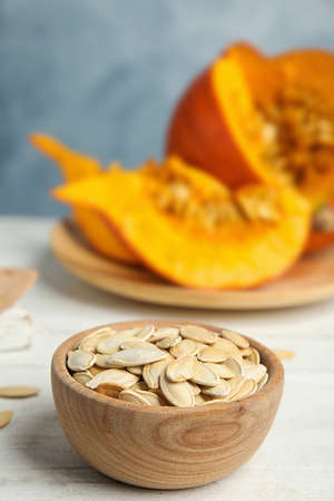 Bowl of raw pumpkin seeds on white wooden table Zdjęcie Seryjne