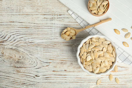 Flat lay composition with raw pumpkin seeds on white wooden table, space for text