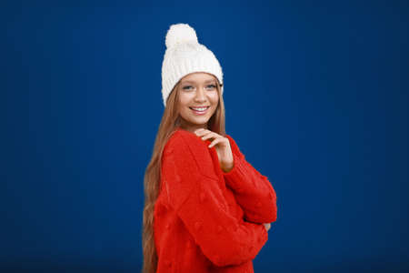 Young woman in warm sweater and hat on blue background. Winter season