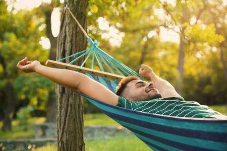Joven descansando en una cómoda hamaca en el jardín verde