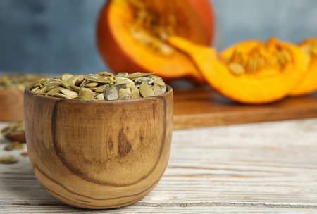 Bowl of raw pumpkin seeds on white wooden table. Space for text Stockfoto - 130074234