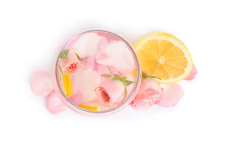 Tasty refreshing lemon drink with roses on white background, top view
