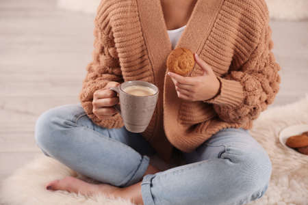Young woman with cup of coffee and cookie on rug at home, closeup. Winter atmosphere