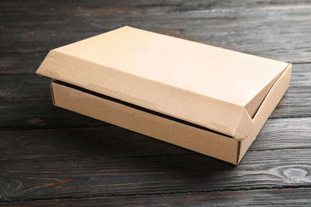 Open cardboard box on black wooden table Stockfoto