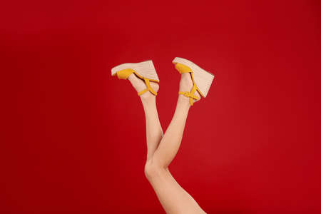 Woman in stylish shoes on red background