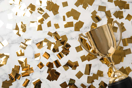 Gold trophy cup and confetti on marble background, flat lay. Space for text Stock fotó