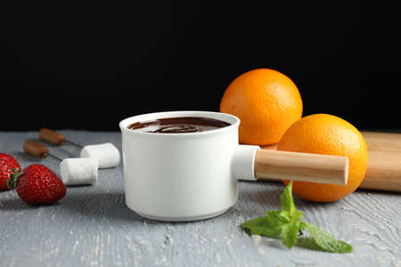 Fondue pot with chocolate, fruits and marshmallow on grey wooden table