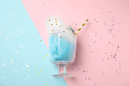 Glass with cotton candy and macaroon on color background, top view