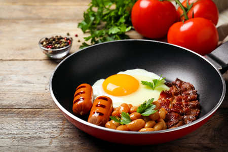 Frying pan with traditional English breakfast on wooden table