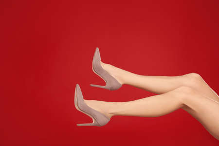 Woman in elegant shoes on red background