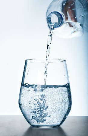 Pouring water from bottle into glass against grey background. Refreshing drink Zdjęcie Seryjne