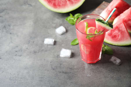Glass of tasty refreshing drink with watermelon on grey table. Space for text