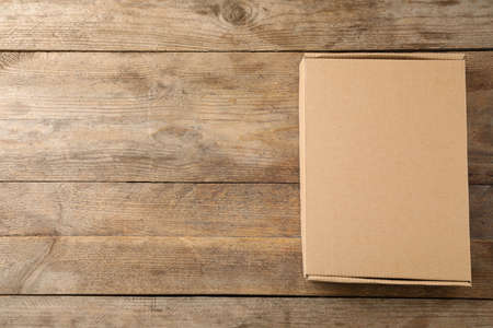 Closed cardboard box on wooden background, top view. Space for text