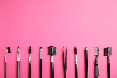 Set of professional eyebrow tools on pink background, flat lay. Space for text 写真素材