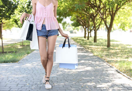 Young woman with shopping bags in sunny park
