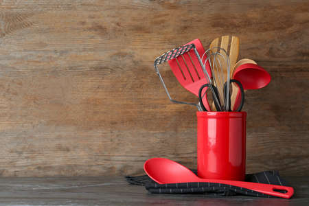 Holder with kitchen utensils on table against wooden background. Space for text
