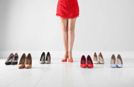 Woman trying on different high heel shoes near light wall, closeup