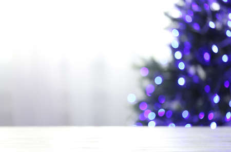 Empty table and blurred fir tree with violet Christmas lights on background, bokeh effect. Space for design