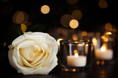 Weiße Rose und brennende Kerzen auf dem Tisch in der Dunkelheit. Begräbnissymbol Standard-Bild