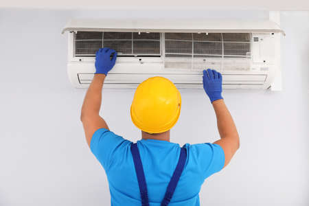 Professional technician maintaining modern air conditioner indoors, back view