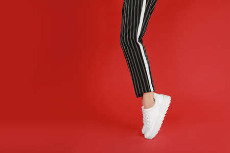 Woman in stylish sport shoes on red background. Space for text 写真素材