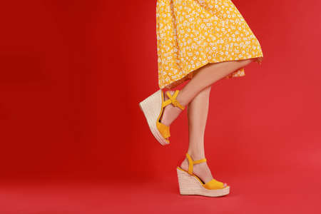 Woman in stylish shoes on red background. Space for text